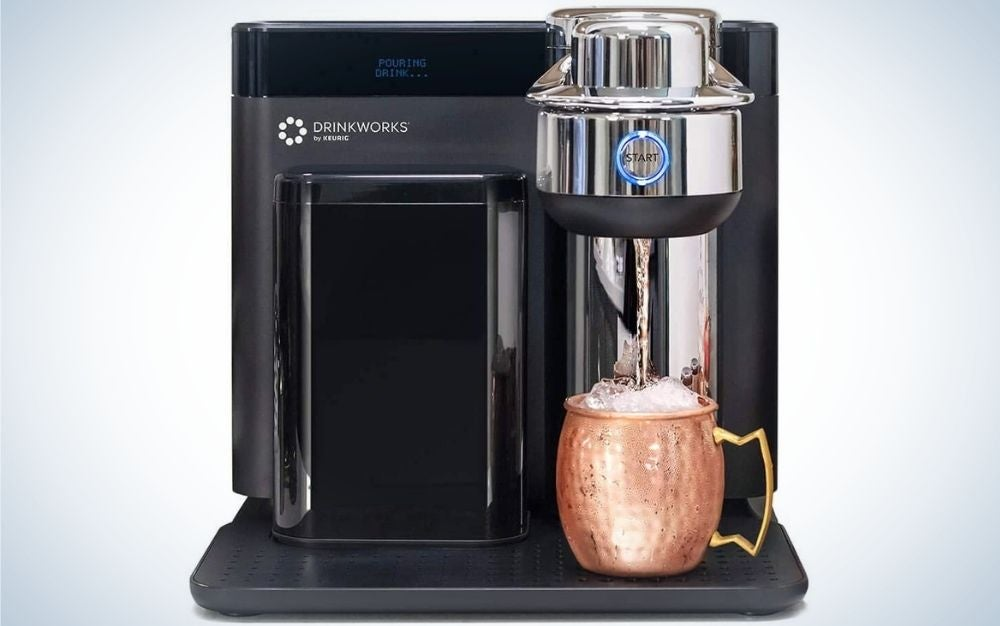 Black Drinkworks Home Bar by Keurig with a gold bottle in it and blue start button on the top of it.