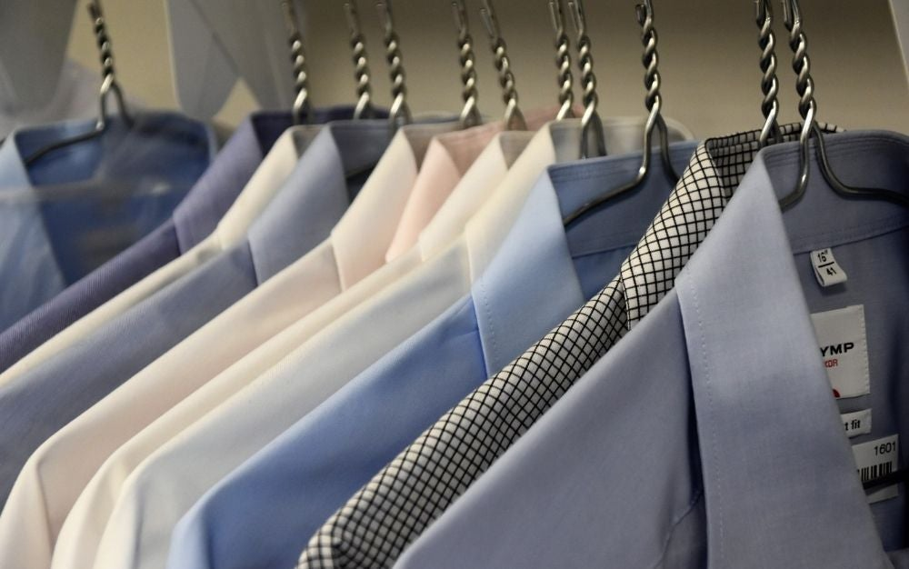 Some shirts in different colors hanging one after the other with silver clothes hangers.
