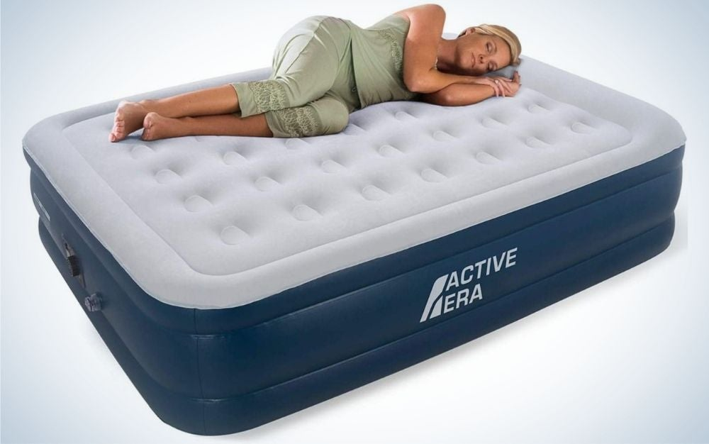 A woman sleeping in a huge air bed with white layer on the top and blue layer with Active Era logo on it.