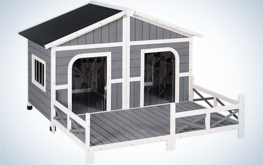 A grey with black roof wooden outdoor dog house with two doors in it.