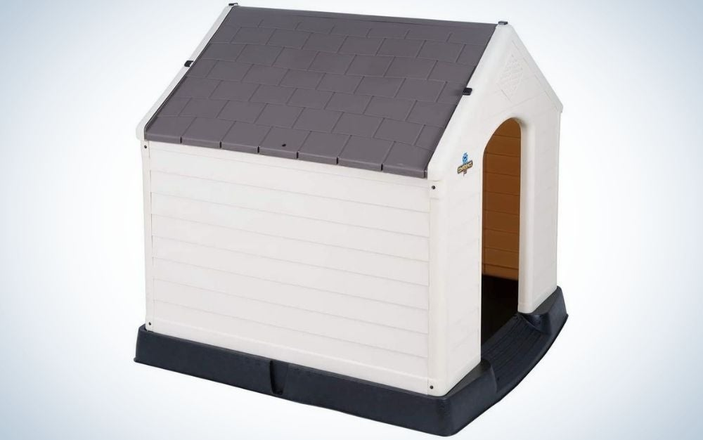 A dog outdoor house designed like a small house with white walls and black roof and floor.