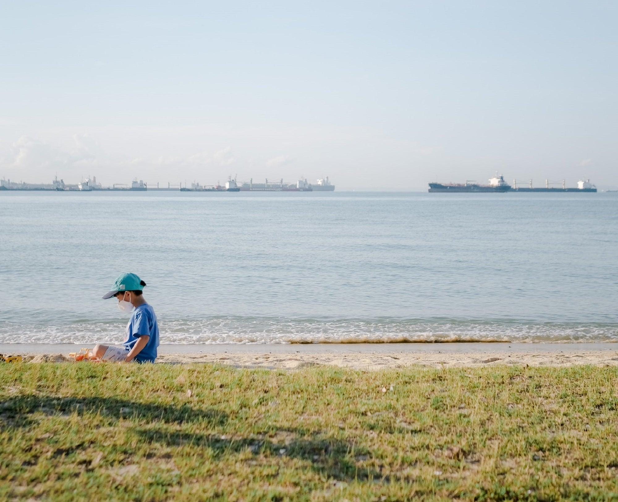 Kid in blue baseball cap and t-shirt sitting on a grassy beach
