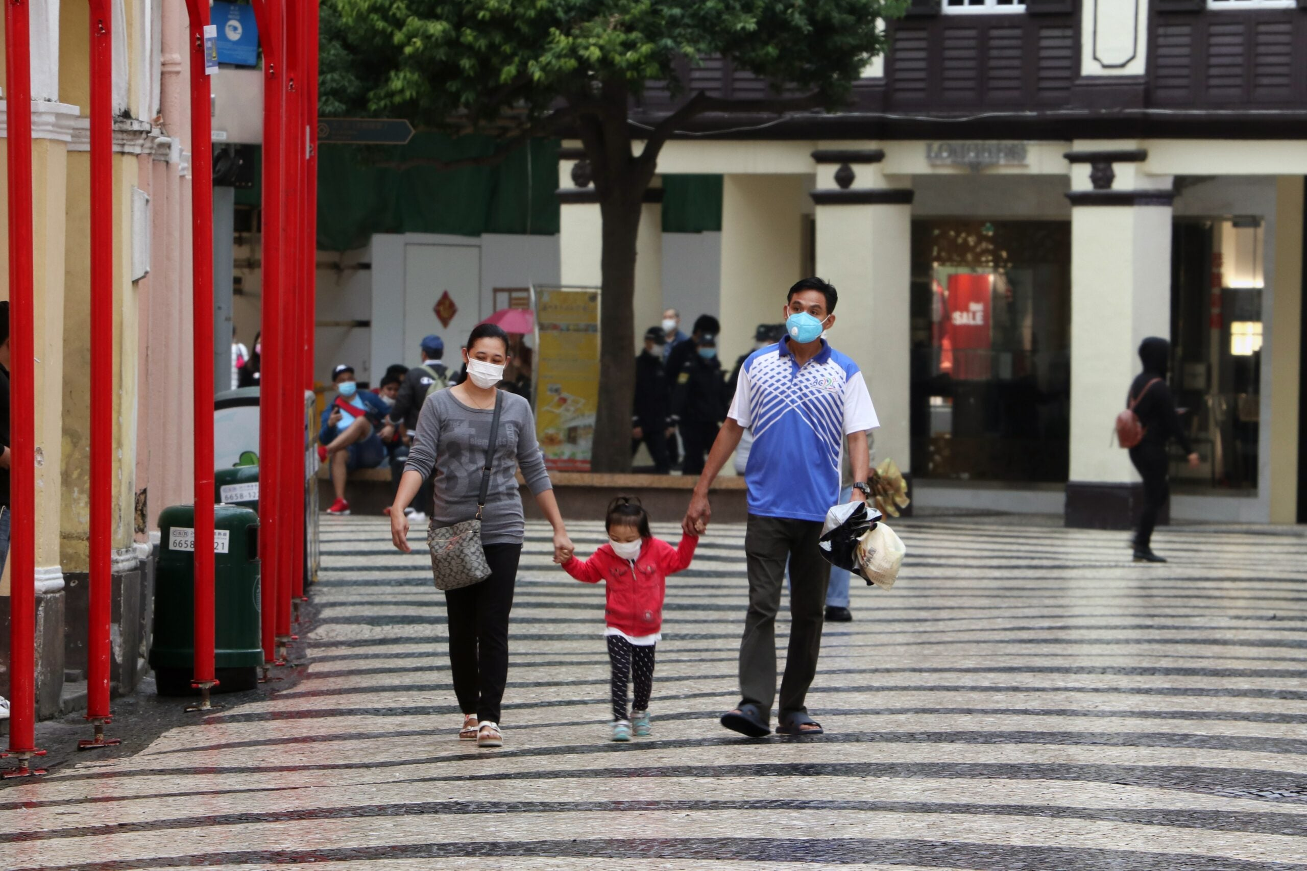 Two adults and a child walk wearing masks.