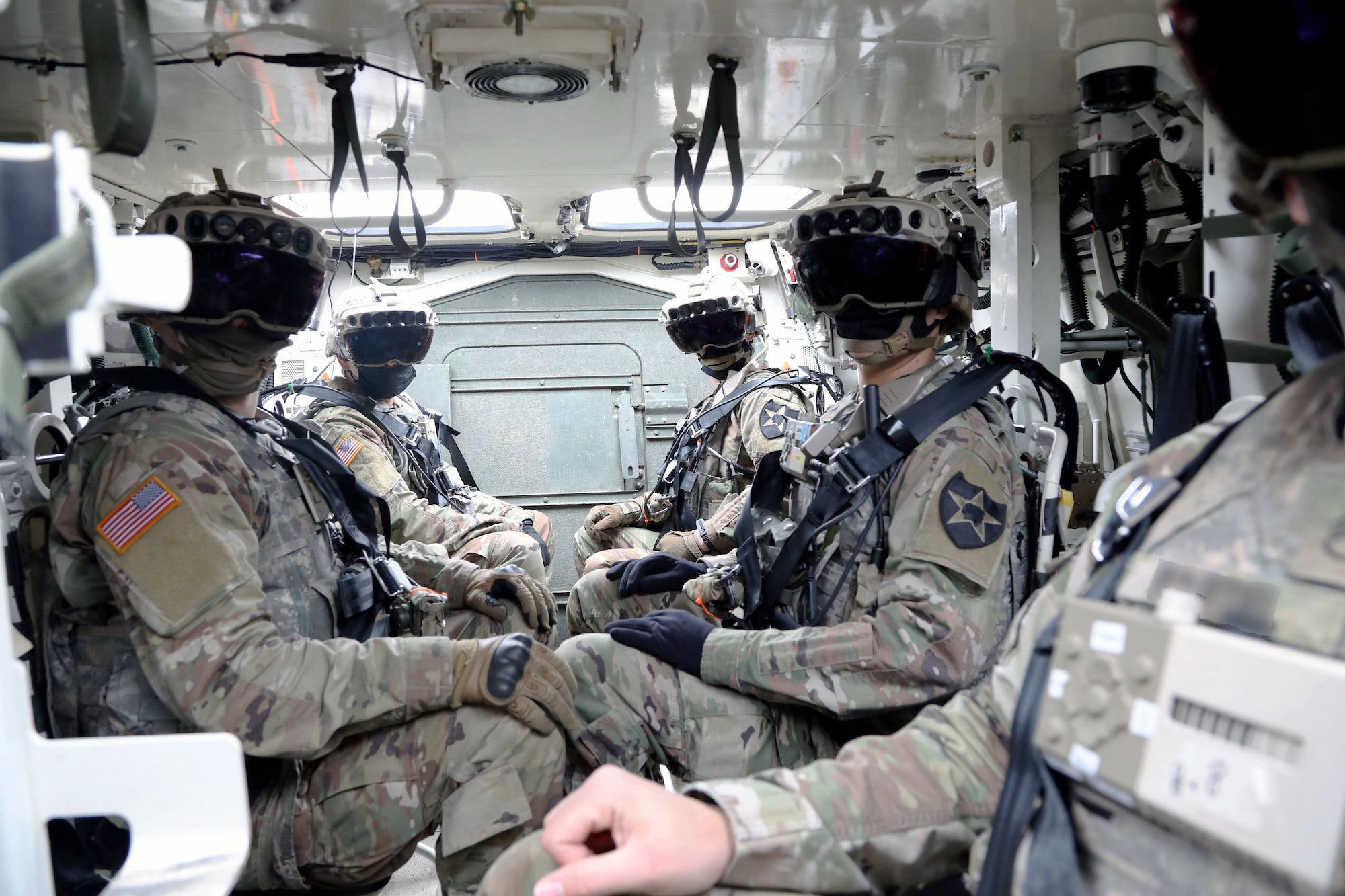 Soldiers wearing augmented reality headsets while sitting in a vehicle.