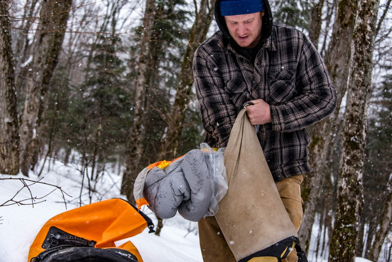 Person stuffing a sleeping bag and plastic bag in a compression bag in the snow
