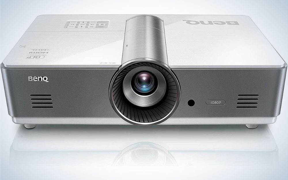 A grey square business projector with a blue lens in the middle of it.