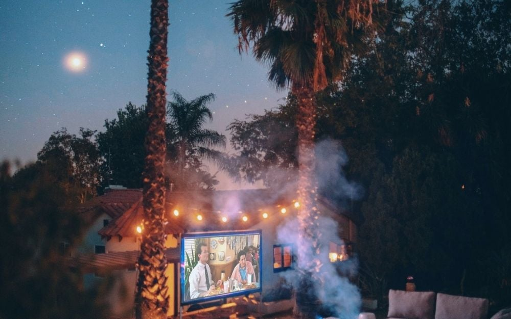 A film set with an outdoor projector with lights in the trees and the smoke of the burning fire.