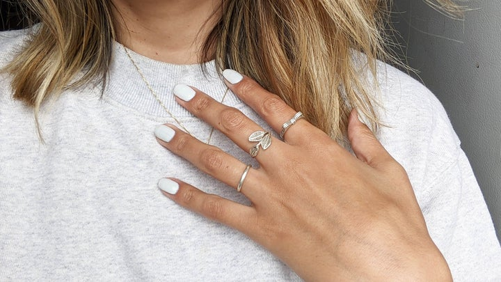 person's hand with silver rings