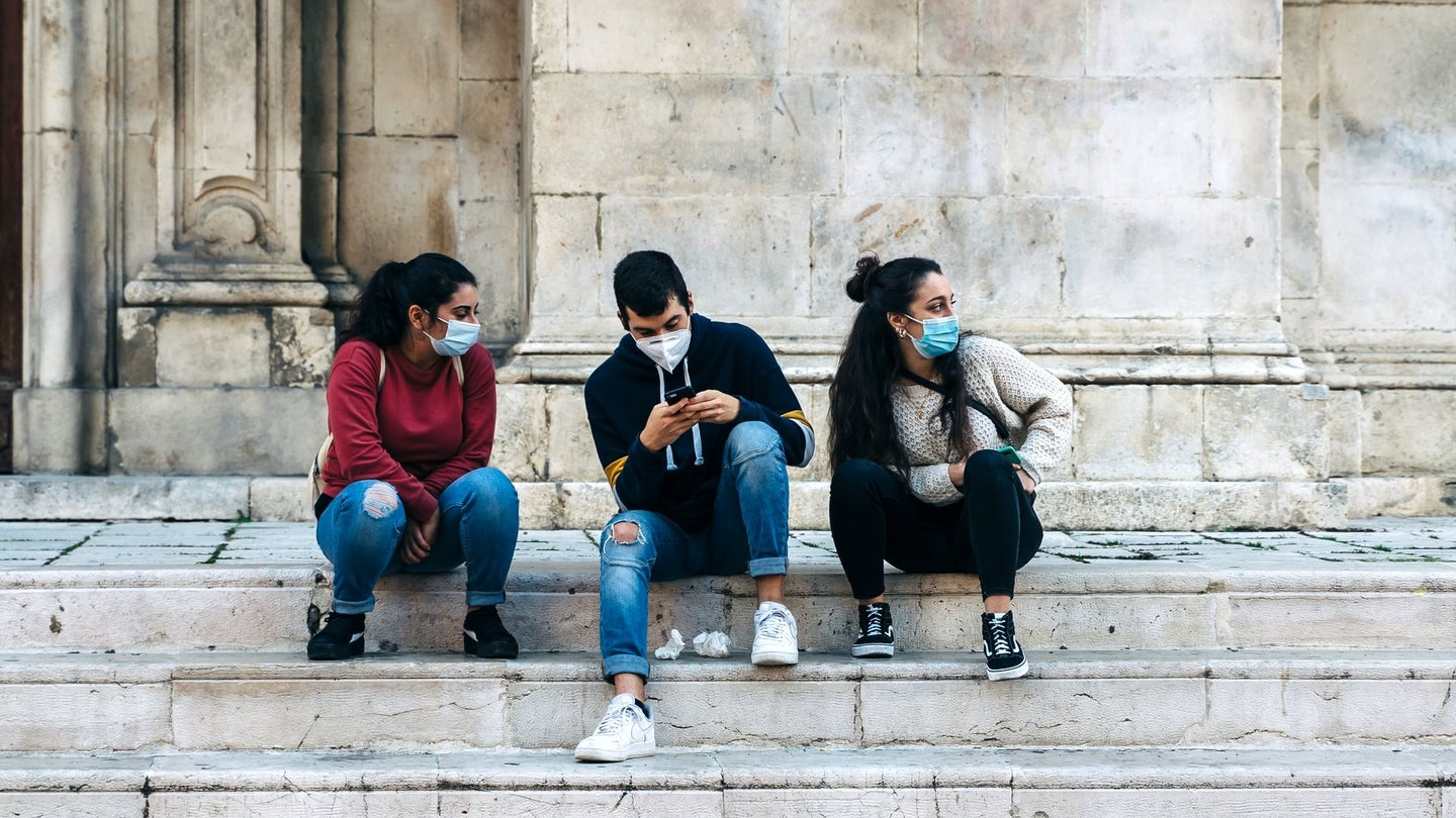 Teens in masks sit on marble stairs.