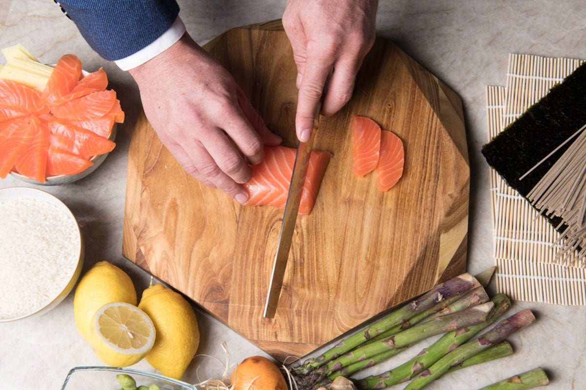 person cutting on a wooden cutting board