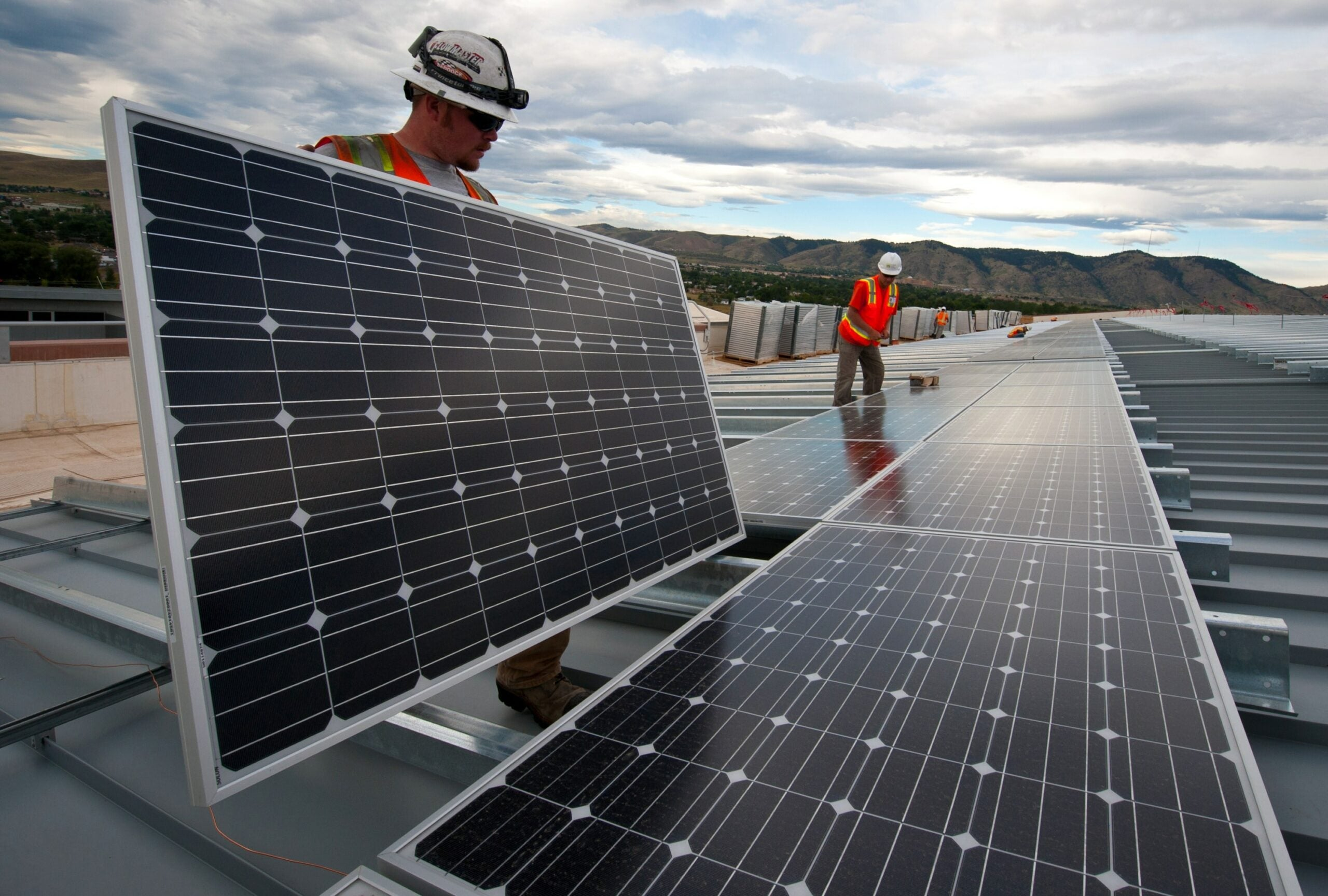 Construction workers install solar panles.