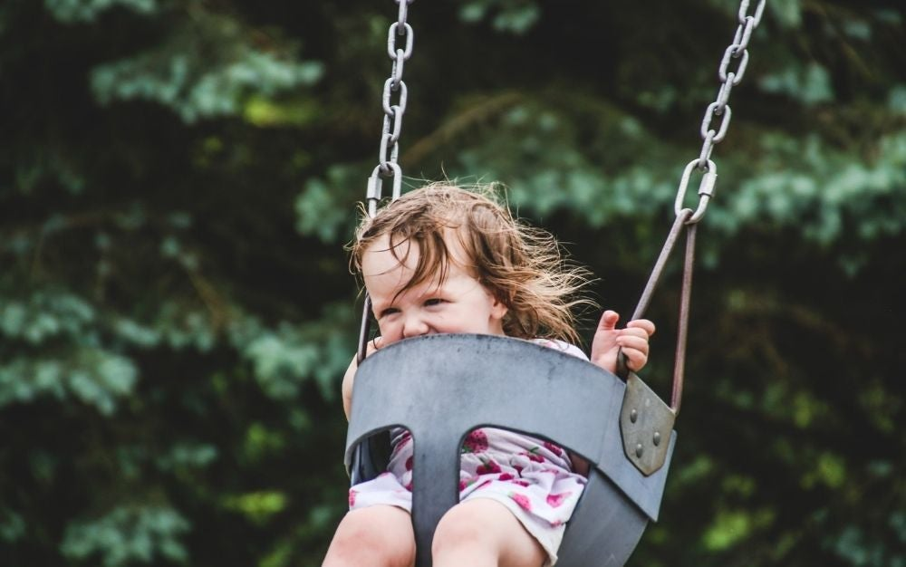 A little happy girl smiling while swinging in a metal swing.