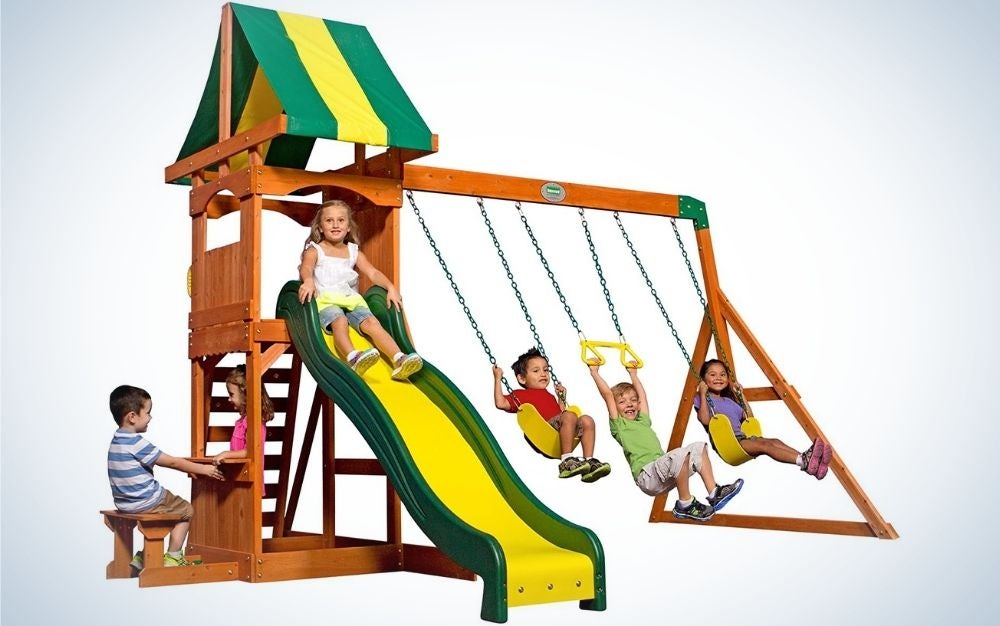 A wooden playset swing set with two standard belt swing set swings and a yellow and green swing trapeze bar into it.