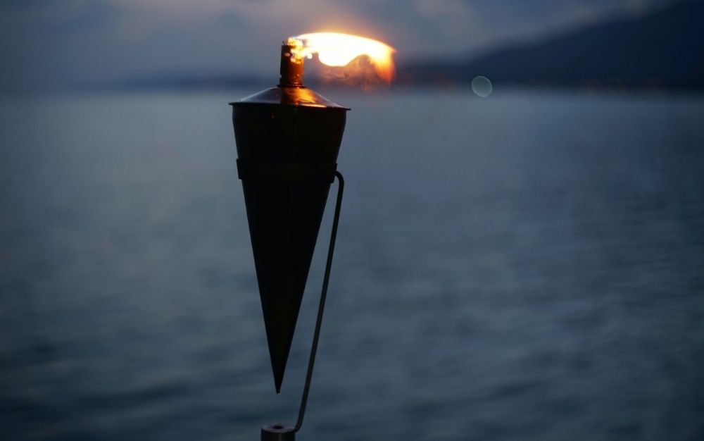 A black tiki torch with flame in a twilight sea background.
