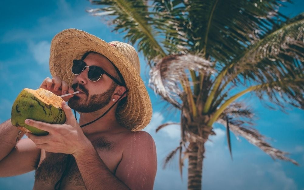 A man drinking coconut on a sunny day and with a palm tree behind him.