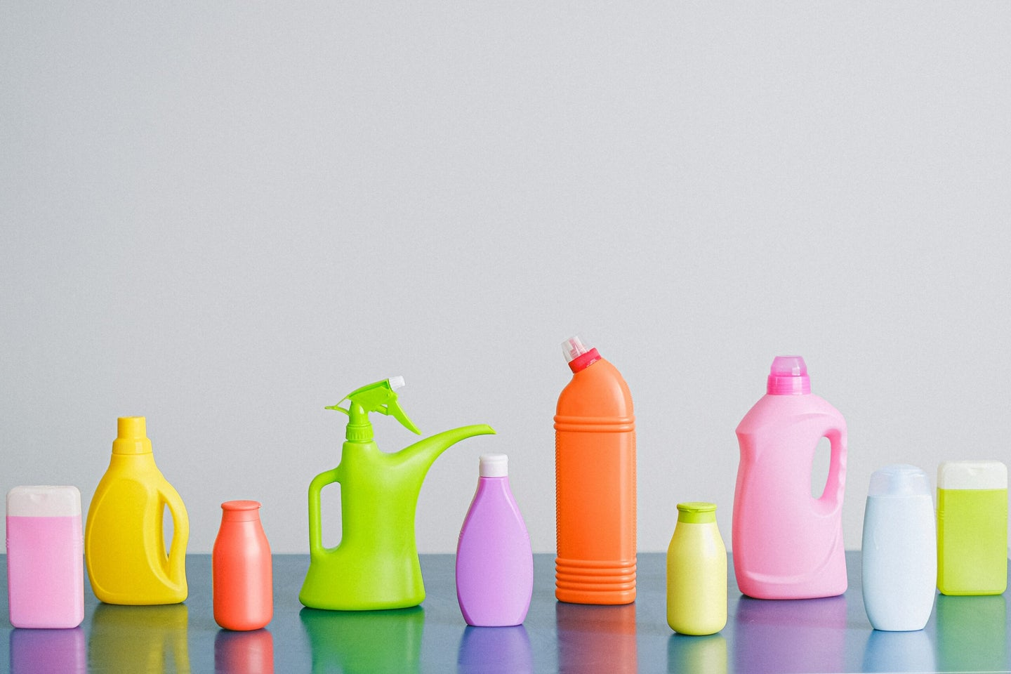 Colorful cleaning products on blank background.
