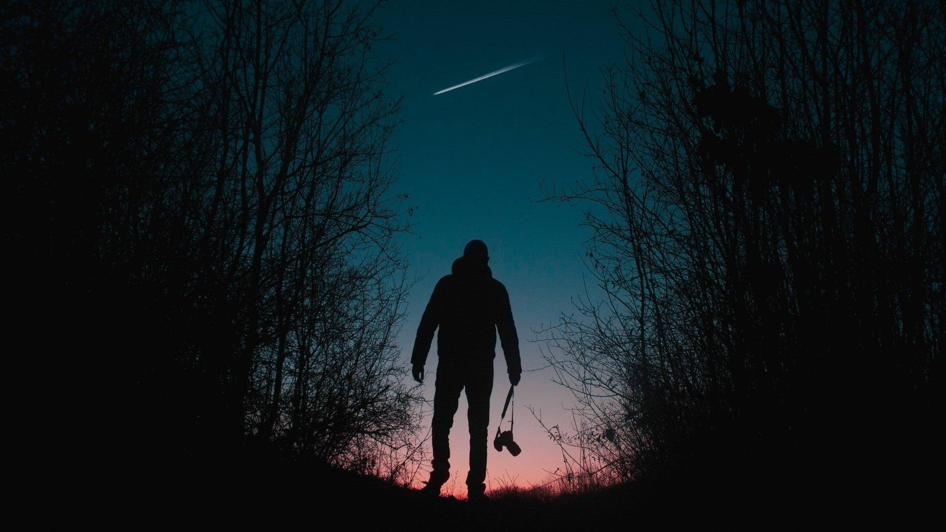 A man walks beneath a shooting star.