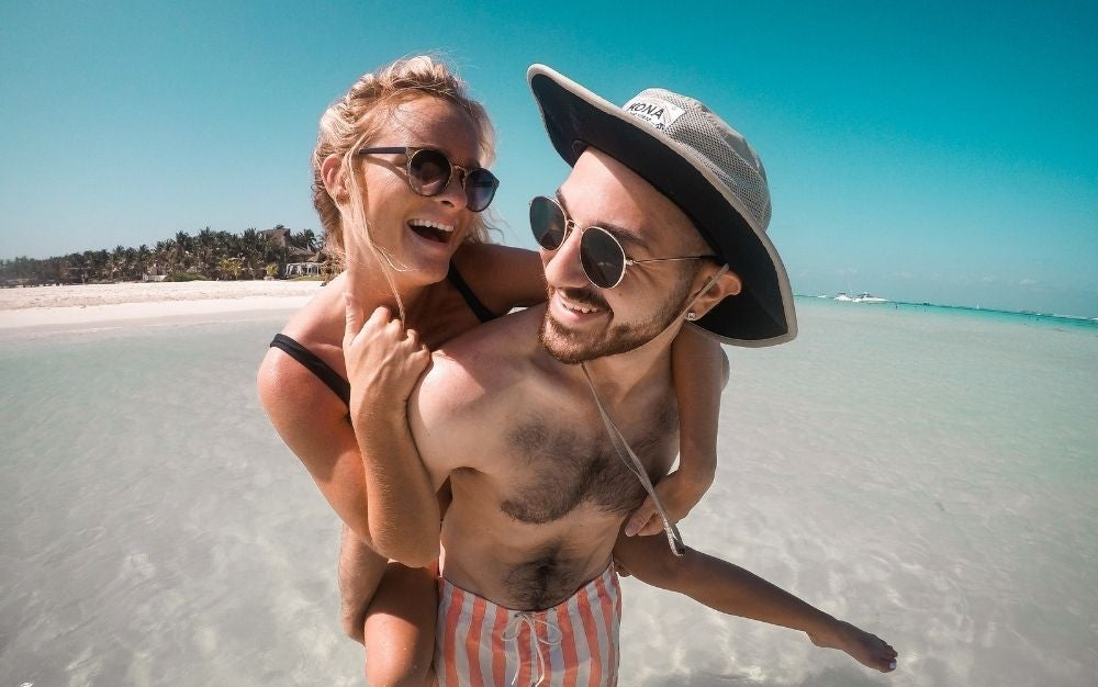 A couple on the beach wearing sunglasses