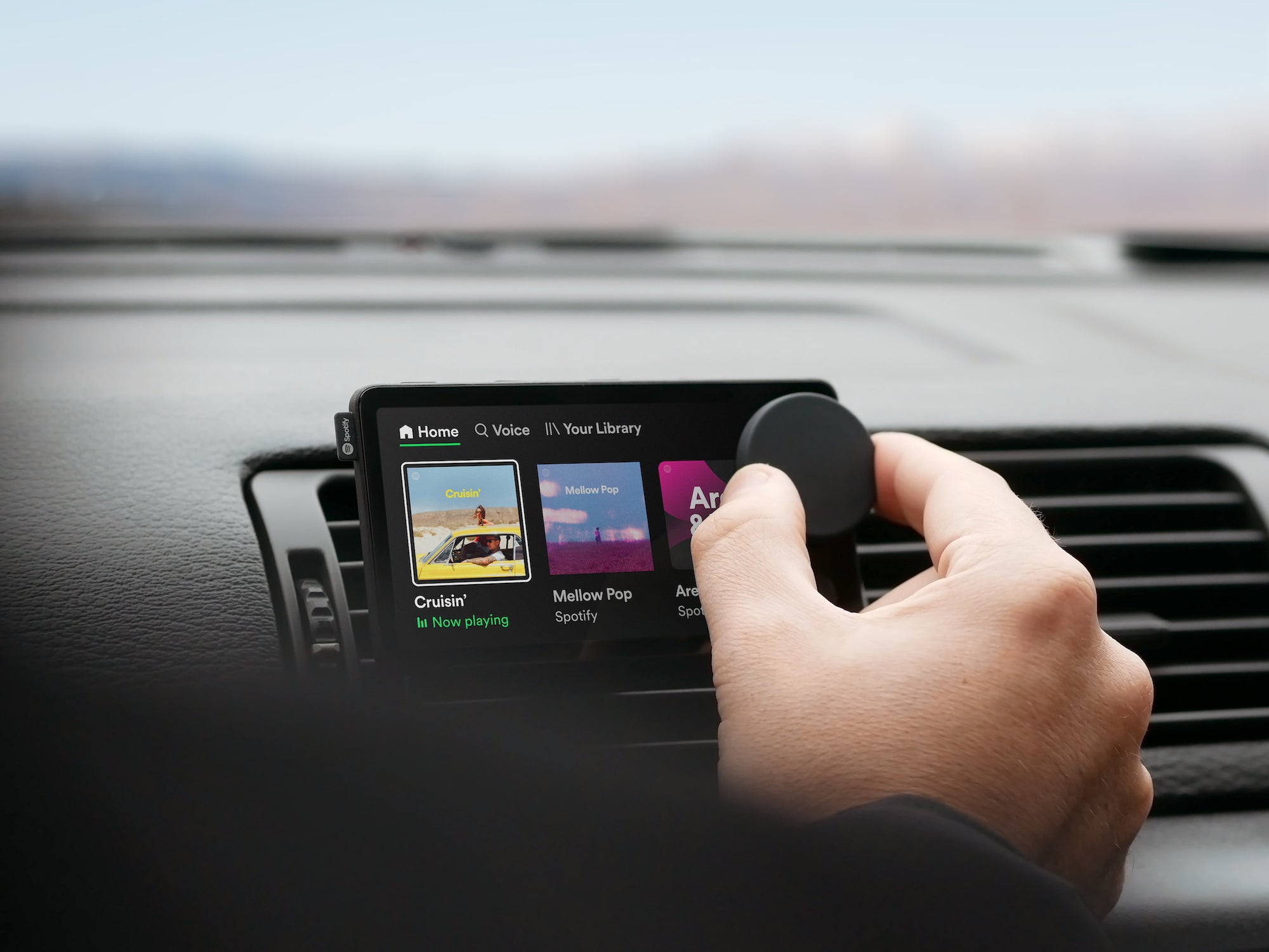 A person controls a knob on Spotify's Car Thing device.