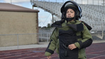 US Army soldier running on a track in a bomb suit