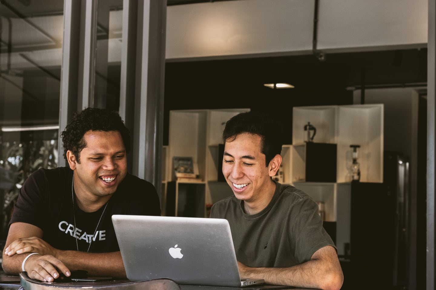 Two young brown people at a Mac laptop