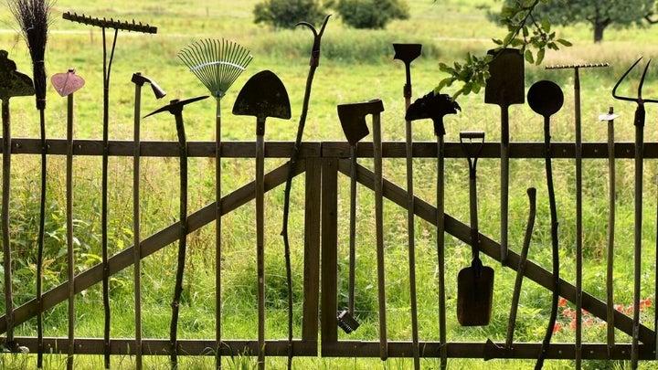 Different gardening tools standing on a wooden garden gate with garden background.