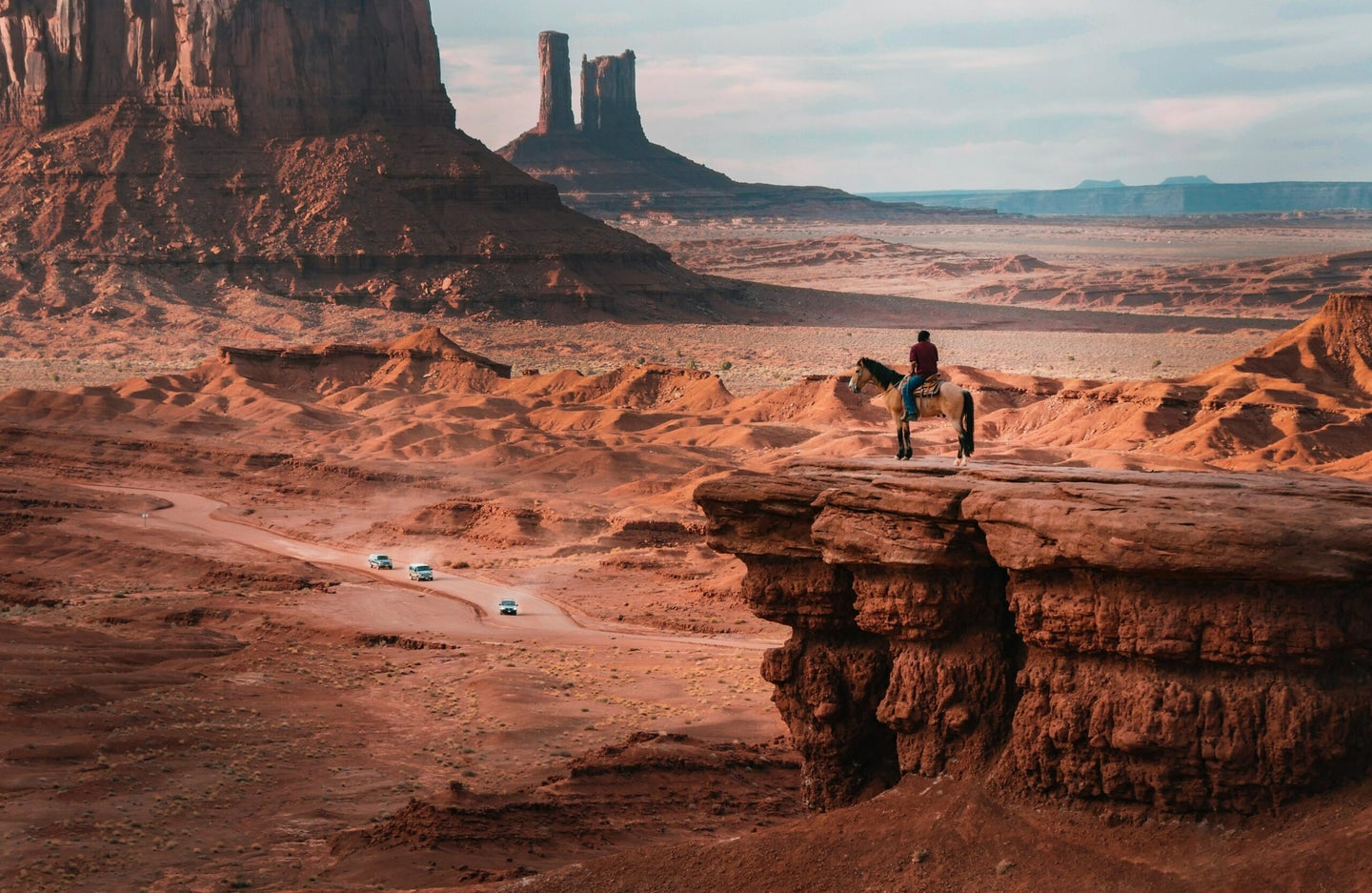 monument valley with person on horse in foreground cars in background