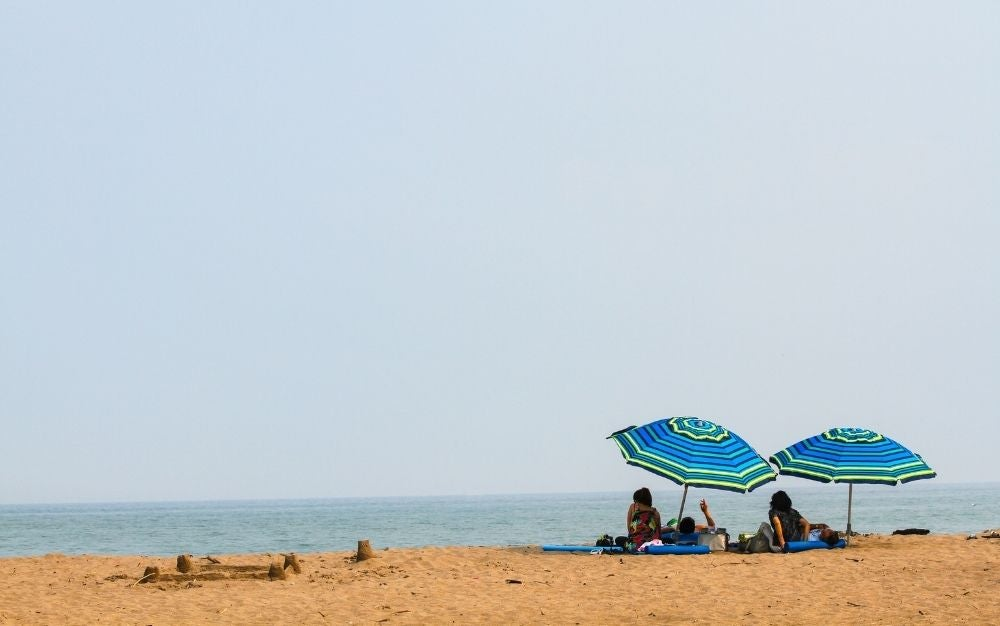 People lying down on the beach under their blue and green umbrella during daytime