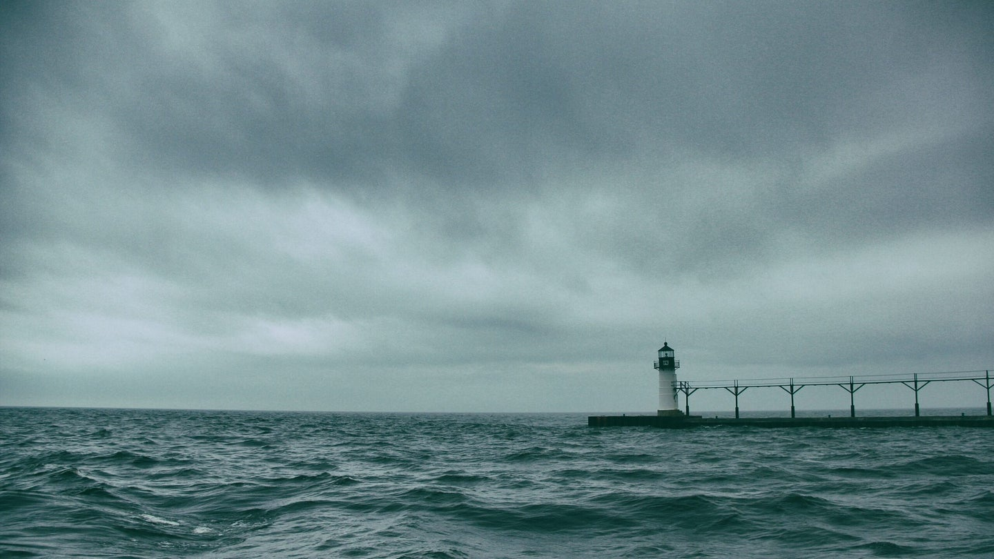 A brewing storm with dark clouds and a lighthouse in Michigan.