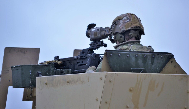 A soldier looks at a gun sight.