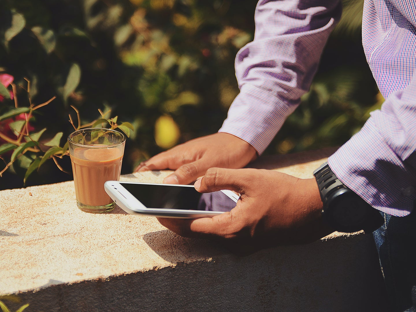 A person standing outside bear a concrete wall, holding their phone with a coffee nearby.