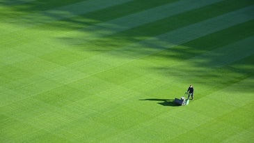 A man using a lawn mower in the middle of a large green field with grass.