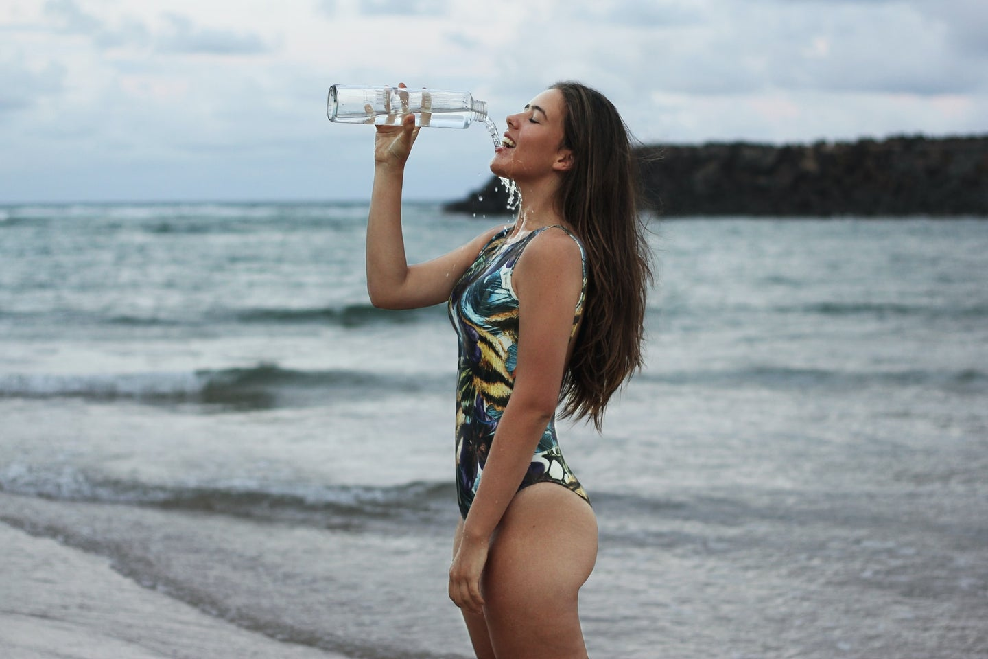 Person in blue swimsuit and long brown hair pouring water out of a clear bottle at the beach