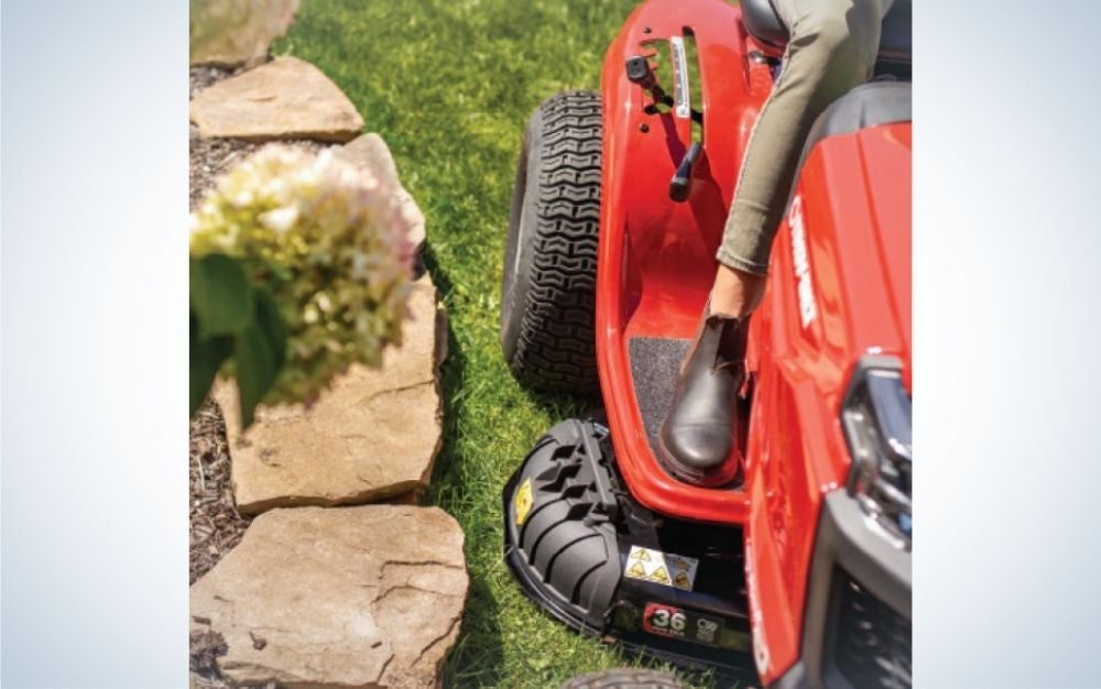 A man riding a lawn mower on the grassy field and some stones in it.