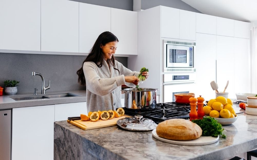 A woman cooking happily in a large kitchen full of food in front of her.