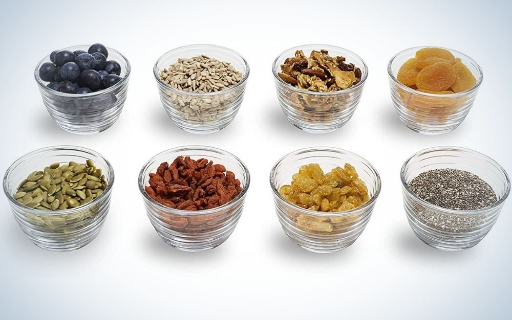 Eight small glass plates filled with different foods such as seeds or cereals, arranged in rows.