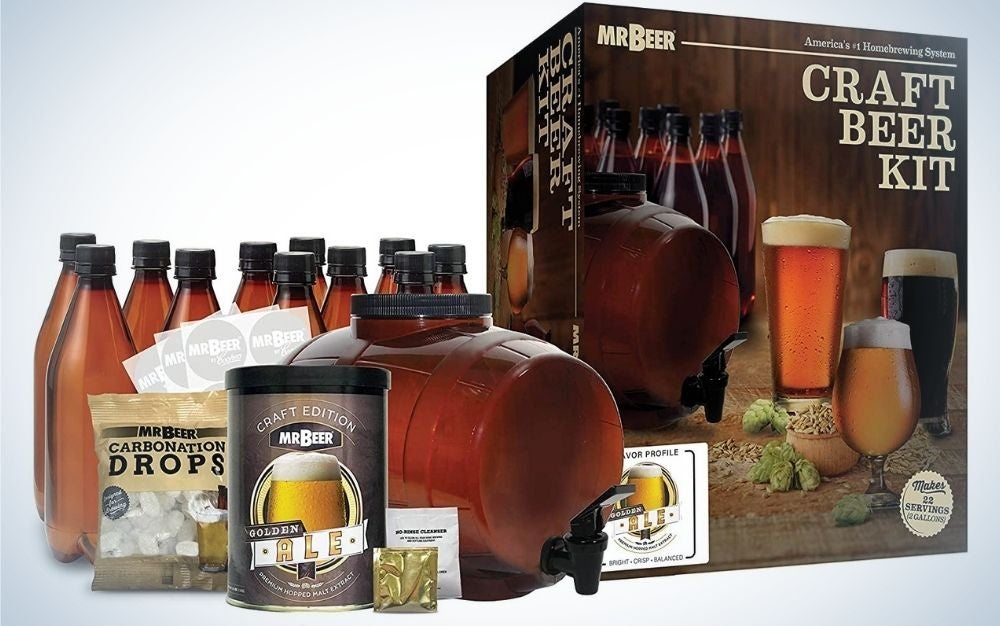 A beer maker with some brown bottles and a box with relevant instructions.