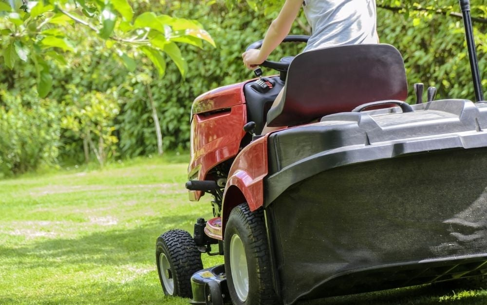 A man riding a lawn mower on the grassy field.