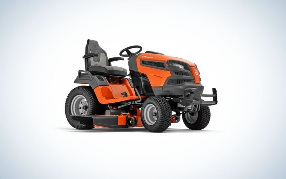 A orange and black lawn mower with 4 black wheels and a black seat as well.