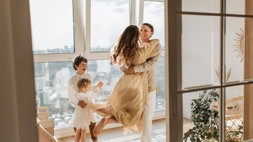 A happy family hugging each other and wearing beige and white clothes.