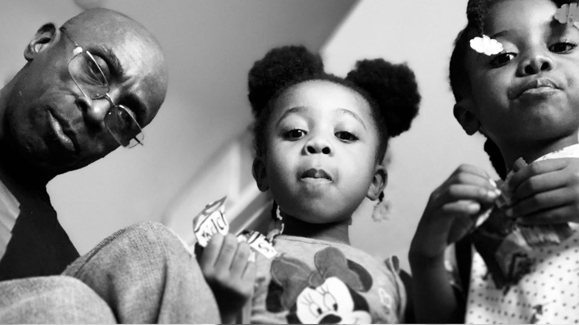 Black father and twin girls looking down at camera