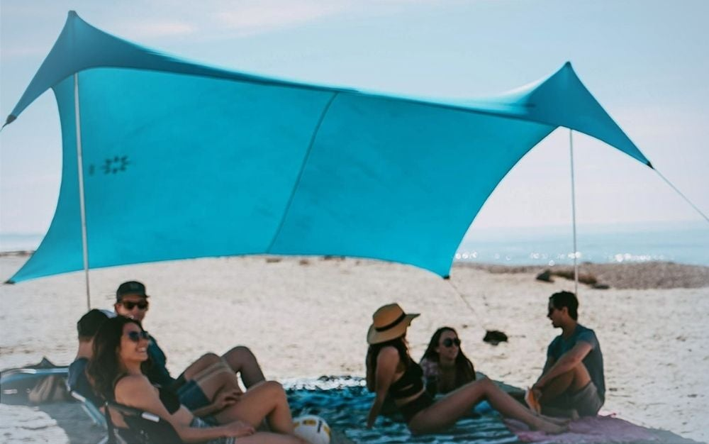 People sitting under a large sky blue beach tent