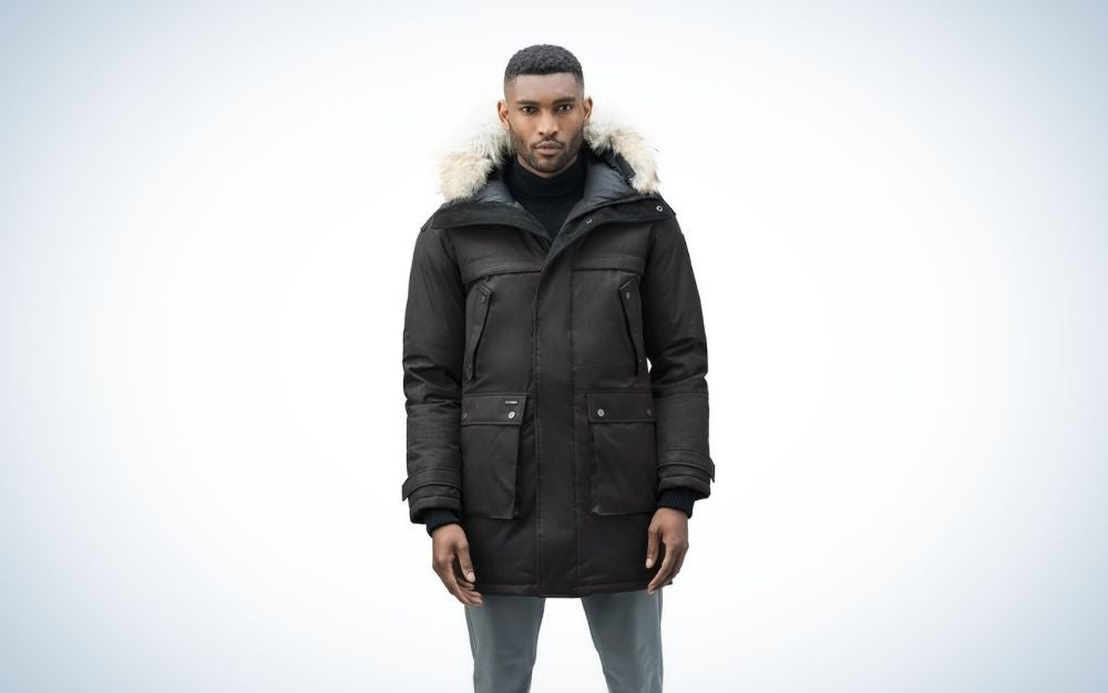A boy posing with a thigh-length winter sweater and two large pockets as well as a stuffed hood on the back.