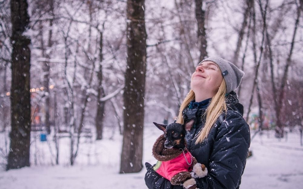 A blonde girl wearing a winter jacket and a dog in her hand as she closes her eyes and is enjoying the snow.