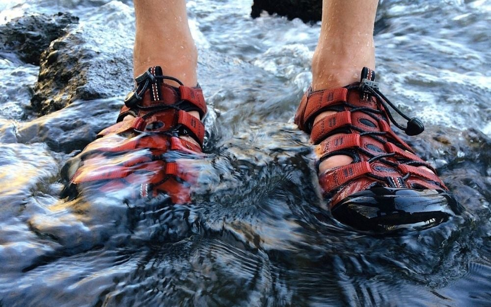 Person wearing red and black water shoes in a river