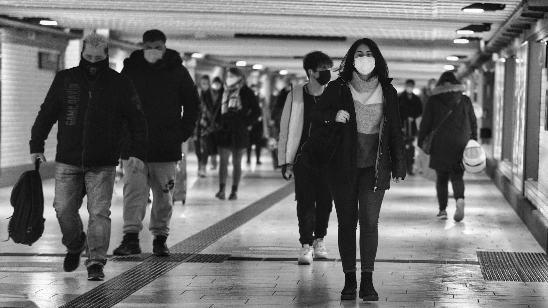 People with masks walk through long hallway.