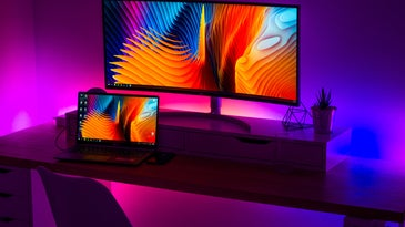 LED strip lights behind a computer desk, adding a purple glow to the room.