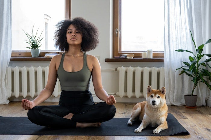 Woman sitting in yoga position next to dog.