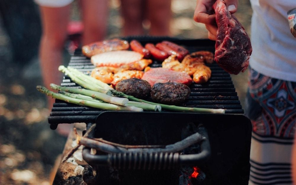 A person cooking meat in grill from side.