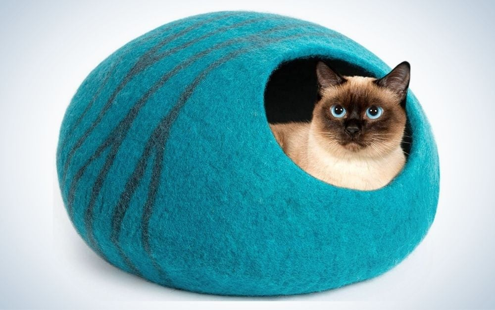 Large, aquamarine, wool cat bed cave with a blue-eye cat in it